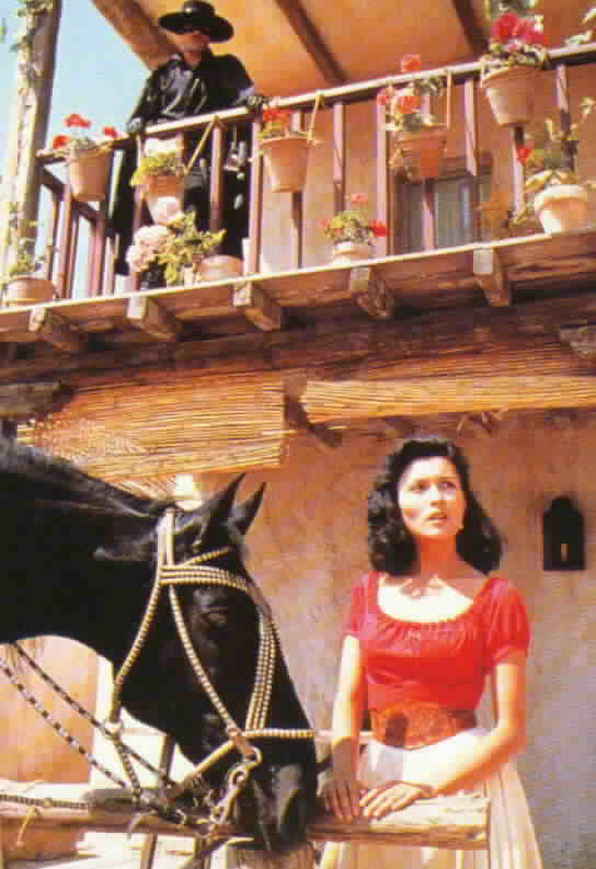Victoria in front of the tavern with Zorro above on the second floor balcony